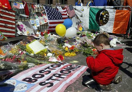 Two-year-old   Wesley Brillant of Natick,   Massachusetts kneels in front of a memorial to the victims of the Boston Marathon bombings near the scene of the blasts on Boylston Street in Boston, Massachusetts, April 21, 2013. REUTERS-Jim Bourg